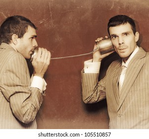 Vintage Photograph Of Two Business People Exchanging Information Down The Line Of A Tin Can Telephone In A Retro Communication Conceptual