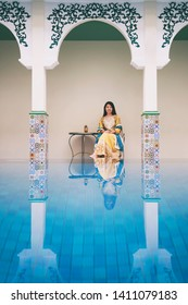 Vintage Photography style of Pertty Asian Tourist girl in Indian or Moroccan style costume at the Indian or Moroccan style pool, outdoor portrait, selected focus.