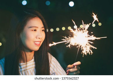 Vintage Photography style of Pretty Asian woman night portrait with Sparkler fairy light bokeh background, selected focus.
