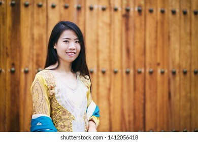 Vintage Photography style of pretty Asian woman at Indian or Moroccan old wooden door, outdoor portrait, selected focus.