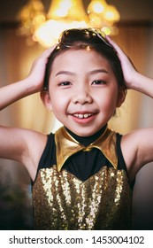 Vintage photography style of pretty Asian girl portrait in golden or yellow dancer style costume, selected focus.