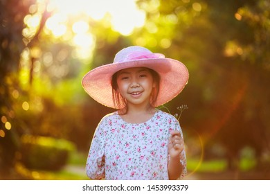 Vintage photography style of pretty Asian girl in pink hat outdoor portrait with sunset sky background, selected focus.