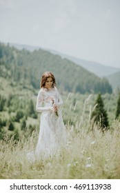 Vintage photography of a young hipster bride posing in wedding dress at sunset in the forest and mountains