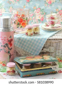 Vintage picnic basket with pink thermos, lemonade jug, tea cups and strawberry shortcakes in an old roses tin