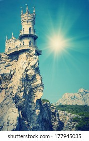 Vintage picture. Castle on the cliff by the sea with a beautiful sun. Swallow's Nest Castle Ukraine Crimea mountain