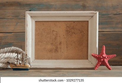 Vintage picture frame with sea shells on wood table top background