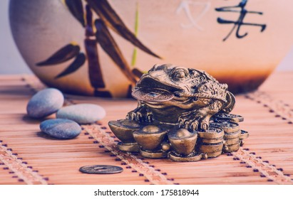 Vintage picture. Gold feng shui frog statuette on a bamboo mat