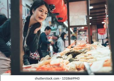 vintage picture of young asian girl photographer picking many seafood sold in Kuromon market in Osaka Japan. chinese woman traveler picking choosing in vendor in black door ichiba osaka japan.