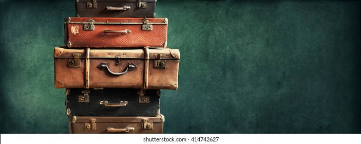 Vintage Pile Ancient Suitcases Form of Tower Design Concept Travel Luggage Traveler on Shabby Black Background Long Format