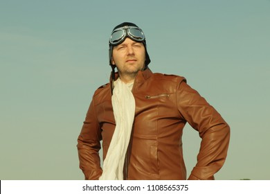 Vintage pilot with leather cap, scarf and aviator glasses  - Portrait of a man in historical pilot clothing
