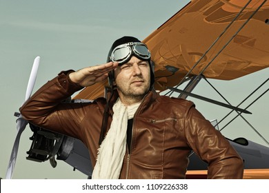Vintage pilot with leather cap, scarf and aviator glasses  - Portrait of a man in historical pilot clothing salutes in front of a historic airplane biplane