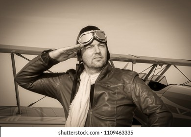 vintage pilot with leather cap, scarf and aviator glasses salutes in front of a historic airplane biplane - Portrait of a man in historical pilot clothing - vintage old picture style