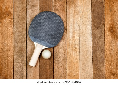 Vintage ping pong paddle on wooden background