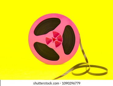 Vintage pink audio reel with recording tape on yellow paper background. Trendy pop art style.