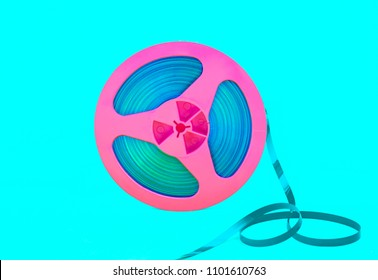 Vintage pink audio reel with recording tape on green background. Trendy pop art style.