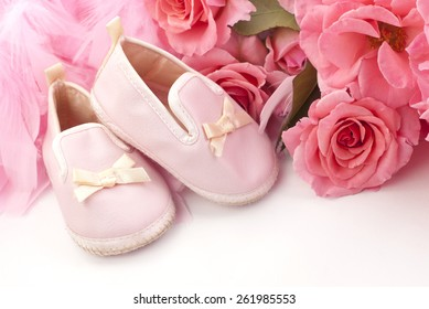 Vintage pink baby shoes with fresh pink roses and pink boa, plenty of space for text