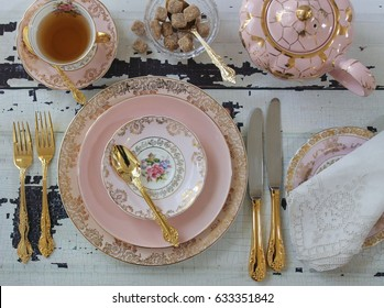 Vintage pink china dinner plates, tea cup, teapot, gold cutlery flatware, sugar cubes in crystal bow, wedding tea party overhead view, on distressed wood table