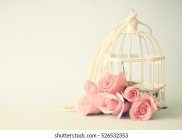 Vintage pink roses in front of a bird cage and pearls