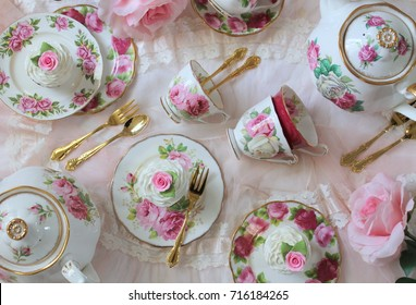 Vintage pink roses tea cups, plates, cup cakes gold teaspoons on lace tablecloth - high tea party