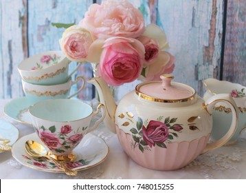 Vintage pink roses teapot, pink and aqua teacups on a lace tablecloth with gold cutlery flatware and a vase of roses - high tea party