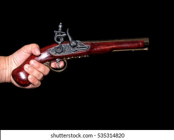 Vintage pistol in hand holding on black background - Prussian antique flintlock pistol with copy space. Hand Holding Vintage gun pistol.