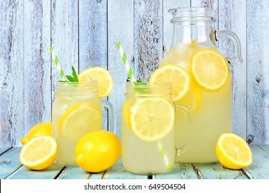 Vintage pitcher of lemonade with two mason jar glasses and lemons on rustic blue wood background
