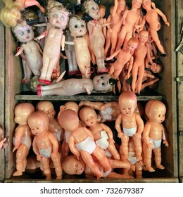 Vintage plastic doll toys of girls, babies, and men in a wooden crate at an antique flea market.