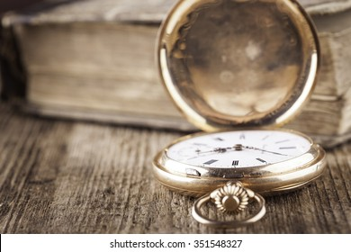 vintage pocket watch and book on wood still life
