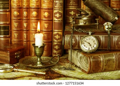 Vintage pocket watch and burning candle in an old candlestick are on the background of antique books