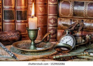 Vintage pocket watch and burning candle in an old candlestick are on the background of antique books as a male adventure concept
