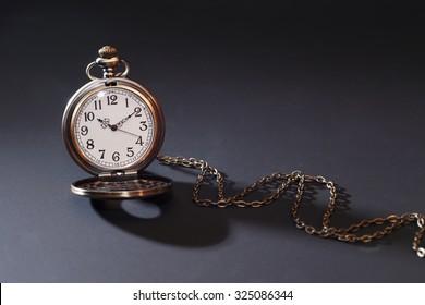 Vintage pocket watch with chain on dark background