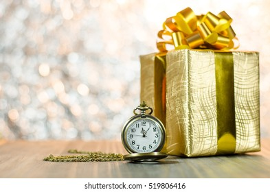 Vintage pocket watch with gold christmas gift box, ribbon and bow on bokeh lights background