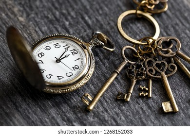 vintage pocket watch with keys on a wooden background