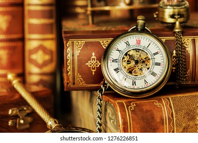 Vintage pocket watch on the background of antique books