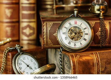 Vintage pocket watch on the background of antique books. Allegory of time