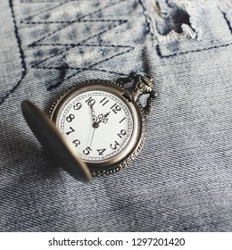 vintage pocket watch on blue jeans, close up