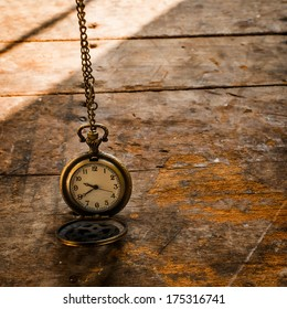 Vintage pocket watch on chain on wooden background with still life.