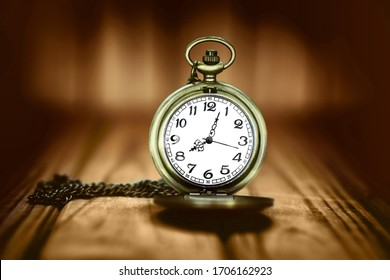 Vintage pocket watch on a wooden background. Selective focus.