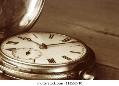 Vintage pocket watch over old timber.  Sepia tone, lots of dust.