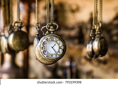 Vintage pocket watchs hanged with chains in an antique shop