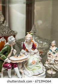 Vintage porcelain figurine couple are playing chess