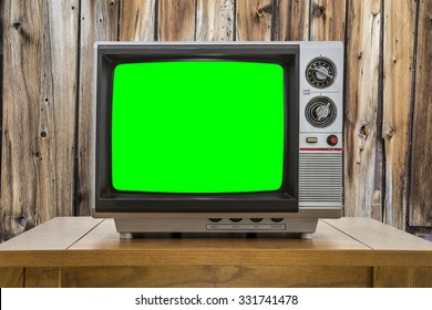 Vintage portable television with chroma key green screen and rustic cabin wall.