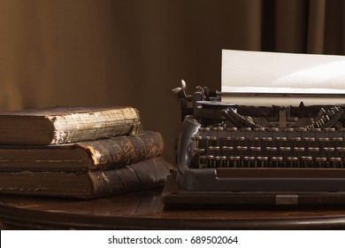 Vintage portable typewriter with a piece of paper and vintage books on a table in brown tones