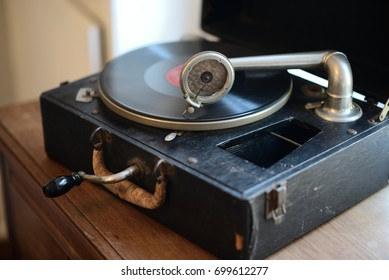 Vintage Portable Victrola record player with spinning record.