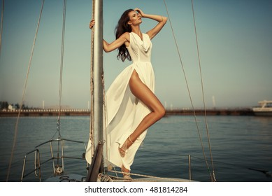 Vintage portrait of beautiful elegant woman in luxury long dress standing on the yacht. High fashion photo.