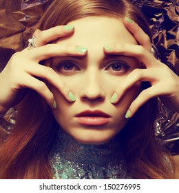 Vintage portrait of beautiful woman with long healthy shiny red (ginger) hair, perfect makeup and stylish silver accessories on her hands. Hands on face. Close up. Retro-futurism style