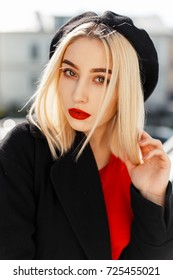 Vintage portrait of a beautiful young blonde woman with red lips in a black coat with a beret on an autumn sunny day