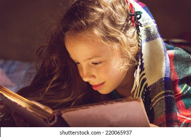 Vintage portrait of cute curly school girl reading a book in cold day