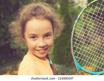 vintage portrait of cute little girl playing tennis in summer