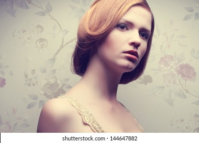 Vintage portrait of a glamorous doll-like retro girl. Healthy ginger (red) hair. Perfect skin. Hollywood style (film noir). Close up. Copy-space. Studio shot